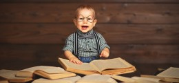 funny baby with books in glasses on a wooden background