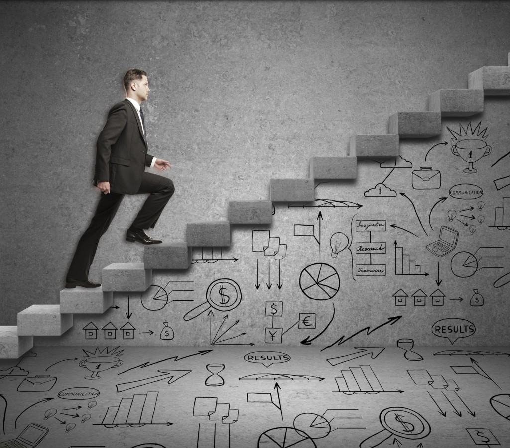 Businessman running upstairs on abstract concrete ladder with business drawings underneath