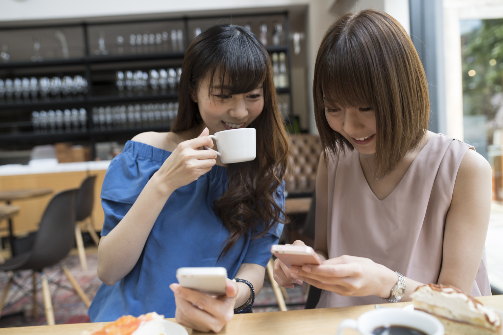 Women are chatting at a cafe while watching smartphones