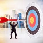 Businessman puts a big dart in the target center