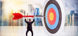 Businessman puts a big dart in the target center