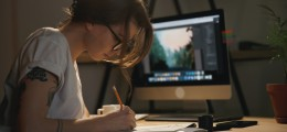 Photo of young woman designer sitting indoors at night drawing sketches in album while using computer.