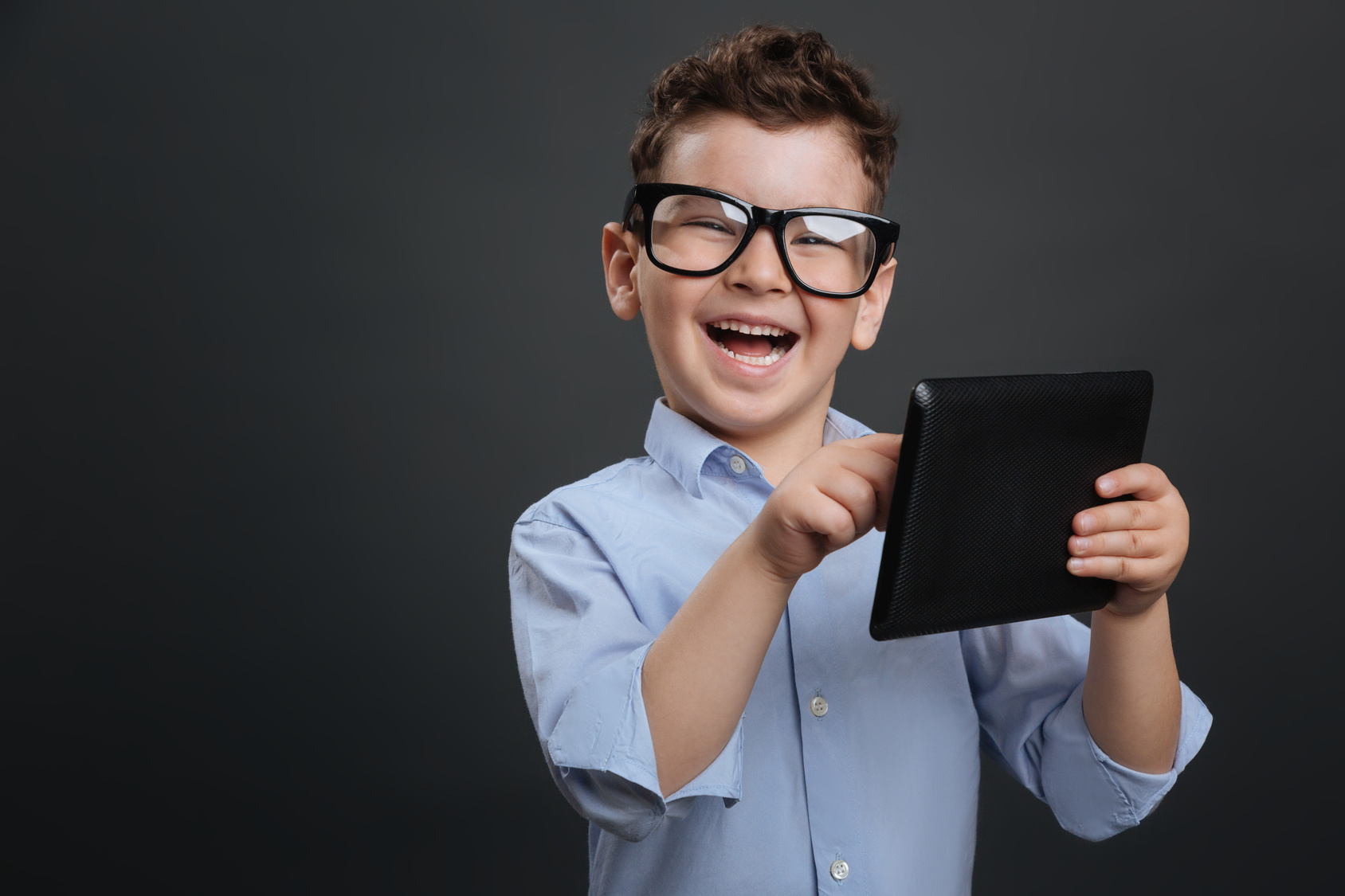 Educative gadget. Diligent clever nice boy using his tablet and looking excited while finding something interesting